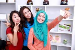 Trzy pięknej kobiety pozuje i robią wyrażeniu podczas gdy takin Fotografia Royalty Free