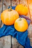 Trzy pięknej pomarańczowej bani na błękitnym ręczniku, drewniany rocznika tło Pojęcie żniwo, Halloween obrazy royalty free