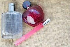 Trzy pięknej szklanej mody cologne wspaniałej buteleczki, pachnidło menchii schudnięcie, czerwony prostokątny z małymi koralikami zdjęcie stock