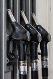 Trzy pistoletu dla refueling przy benzynową stacją Zdjęcie Royalty Free