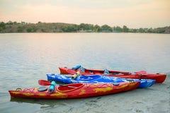 Trzy Podróżnego kajaka na piasek plaży blisko Pięknej rzeki lub jeziora przy wieczór Podróży i przygody pojęcie Obraz Stock