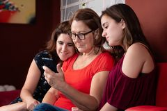 Trzy pokolenia latynoskie kobiety patrzeje smartphone obraz royalty free