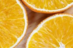 Trzy pomarańczowego plasterka Zbliżenie plasterki na desce drewno Obrazy Stock