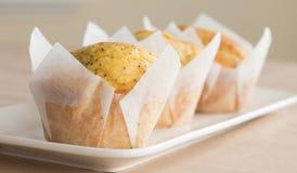Trzy Pomarańczowy i Makowego ziarna Muffins na bielu talerzu Obrazy Royalty Free