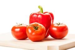 Trzy pomidoru i czerwonego pieprz na drewnianej desce Zdjęcie Royalty Free