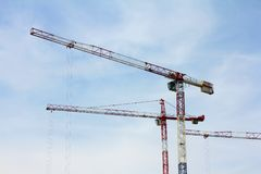 Trzy potężnego budowa żurawia przeciw niebu, podczas gdy pracujący Budowa obrazy stock