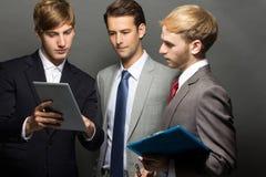 Trzy pracownika dyskutuje plany biznesowych Zdjęcie Royalty Free