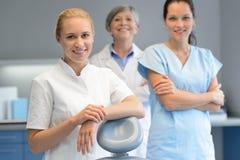 Trzy profesjonalistów dentysty kobieta przy stomatologiczną operacją Obrazy Stock