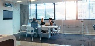 Trzy projektanta dyskutuje w spotkanie sala Zdjęcia Stock