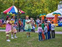 Trzy przebierali kobiety i grupy dzieci bawić się w fre Fotografia Stock