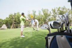 Trzy przyjaciela bawić się golfa na polu golfowym, ostrość na caddy Fotografia Stock