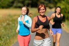 Trzy przyjaciela biega outdoors ono uśmiecha się Zdjęcie Royalty Free