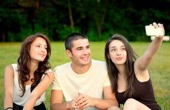 Trzy przyjaciela bierze fotografie outside i uśmiechnięte zdjęcia royalty free