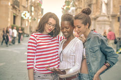 Trzy przyjaciela ogląda ekran pastylka zdjęcia royalty free
