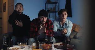 Trzy przyjaciela ogląda sport grę na tv, martwi się o drużynowym przegrywaniu Faceci siedzi na kanapie z piwem w domu i zbiory