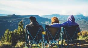 Trzy przyjaciela siedzą w campingów krzesłach na górze góry, podróżnicy cieszą się naturę i cuddle, turysty spojrzenie w odległoś obrazy stock