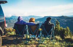 Trzy przyjaciela siedzą w campingów krzesłach na górze góry, podróżnicy cieszą się naturę i cuddle, turysty spojrzenie w odległoś obraz royalty free