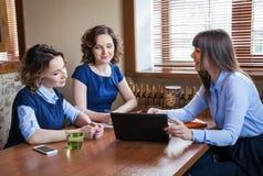 Trzy przyjaciela w cukiernianym działaniu na laptopie Obraz Royalty Free