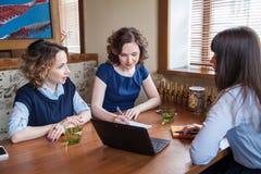 Trzy przyjaciela w cukiernianym działaniu na laptopie Fotografia Royalty Free