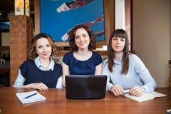Trzy przyjaciela w cukiernianym działaniu na laptopie Zdjęcia Stock