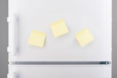 Trzy puste miejsce papieru żółtej kleistej notatki na białej chłodziarce Obrazy Stock