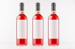 Trzy różanej wino butelki z pustymi biel etykietkami na białej drewnianej desce, wyśmiewają up Fotografia Stock
