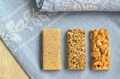 Trzy różnego typ gozinaki bary z słonecznikowymi ziarnami, arachidami i sezamowymi ziarnami na błękitnym tablecloth tle z embroid zdjęcia royalty free