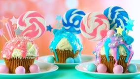 Trzy różowy i błękitne odkrywczość babeczki dekorowali z cukierku i ampuły lizakami obraz stock