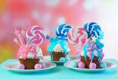 Trzy różowy i błękitne odkrywczość babeczki dekorowali z cukierku i ampuły lizakami fotografia stock