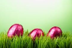 Trzy różowego foliowego Wielkanocnego jajka na trawie Zdjęcia Stock