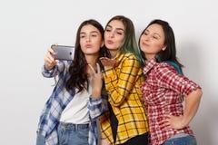 Trzy radosnej dziewczyny dziewczyny robi? selfie u?miecha si? Na bia?ym tle zdjęcie royalty free