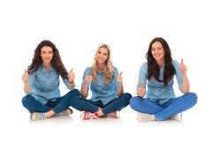 Trzy relaksowali przypadkowe kobiety siedzi ok znaka i robi fotografia stock