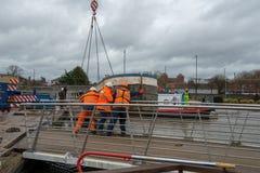 trzy robociarza w pomarańczowych kamizelkach obniżają łódź w kanał Zdjęcie Royalty Free