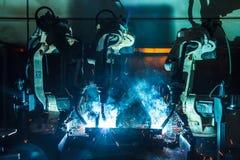 Trzy robotów spaw w samochodzie rozdziela fabrykę Obrazy Stock