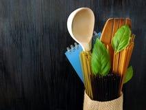 Trzy rodzaju spaghetti, drewniana łyżka i notatnik dekorujący z basilów liśćmi na ciemnym tle, Obraz Royalty Free