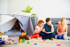 Trzy rodzeństwa czyta książkę zdjęcia royalty free