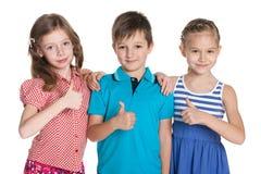 Trzy rozochoconego dziecka trzymają jego aprobaty Obrazy Royalty Free