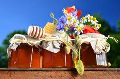 Trzy słoju pełno wyśmienicie świeży miód, kawałek honeycomb miodowa chochla i dzicy kwiaty w pasiece, Zdjęcia Stock