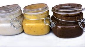 Trzy słoju z białym, żółtym i brown miodem, Obrazy Stock