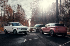 Trzy samochodu Land Rover Range Rover parkujący przy jesieni lasową asfaltową drogą przy pogodnym dniem Obrazy Royalty Free