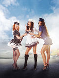 Trzy seksownej żeglarz kobiety stoi w porcie Fotografia Stock