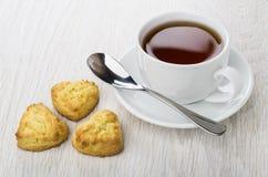 Trzy shortbread ciastka, filiżanka herbata, teaspoon na spodeczku obraz royalty free