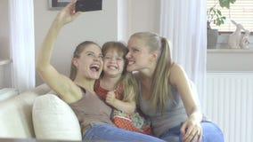 Trzy siostry trzyma up smartphone brać obrazek w różnym wieku w domu zbiory