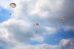 Trzy spadochroniarza skaczą z spadochronami na niebieskim niebie z białym chmury tłem zdjęcia stock