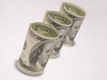 Trzy staczali się w górę sto dolarowych rachunków na białym tle Obrazy Royalty Free