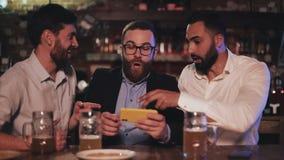 Trzy starego przyjaciela ogl?da wideo na smartphone i pije szkicu piwo w sporta barze Przyjaciele ?mia si? i dyskutuj? zbiory wideo