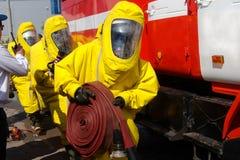 Trzy strażaka w ochronnych kostiumach i maskach gazowych przygotowywają gasić ogienia obrazy stock