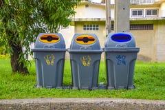 Trzy szarego kubła na śmieci lokalizować wzdłuż ścieżki w parku, Rzuca śmieci w grat, Zadawalają pomoc utrzymywać czysty Domy zdjęcia stock