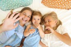 Trzy szczęśliwej małej siostry na łóżkowym mieć zabawę zdjęcia stock