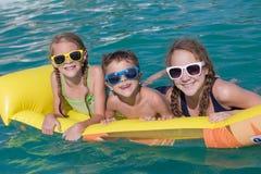 Trzy szczęśliwego dziecka bawić się na pływackim basenie przy dniem Tim Zdjęcia Royalty Free